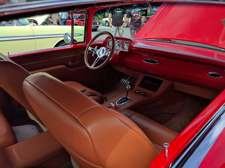 Image shows dashboard and driver controls of the 57 Bel Air custom. The removable iPad is integrated into the center console. This technology controls most of the classic's electronics.
