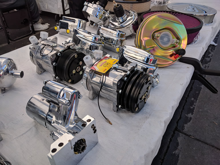 Image of polished motor parts for customized cars. Airconditioning compressors, starter motors, brake boosters, and brake reservoirs.