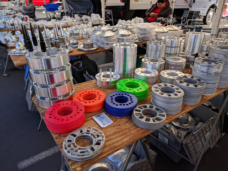 Lugnut king Raul Gonzalez's display of wheel spacers, decorative lug nuts, hub caps and wheel centers in swap meet alley at Alameda Fairgrounds