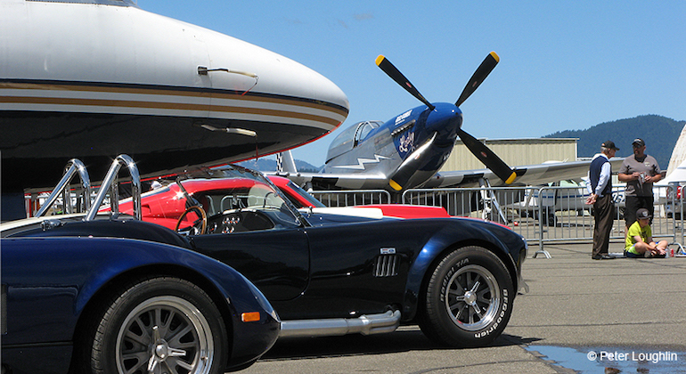 Image of fighter plane with classic car Cobras
