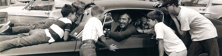Carroll Shelby sitting in a Mustang and surrounded by children