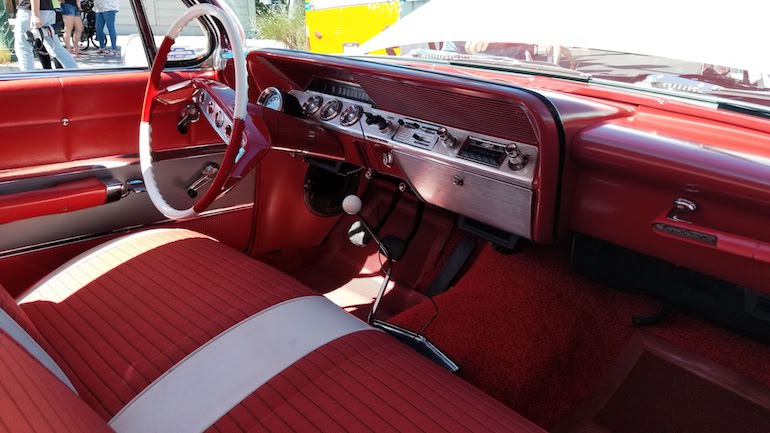 Image of dashboard and interior of 1961 Chev SS Impala 409 cubic inch with column mounted tachometer, sports steering wheel, and SS grab handle