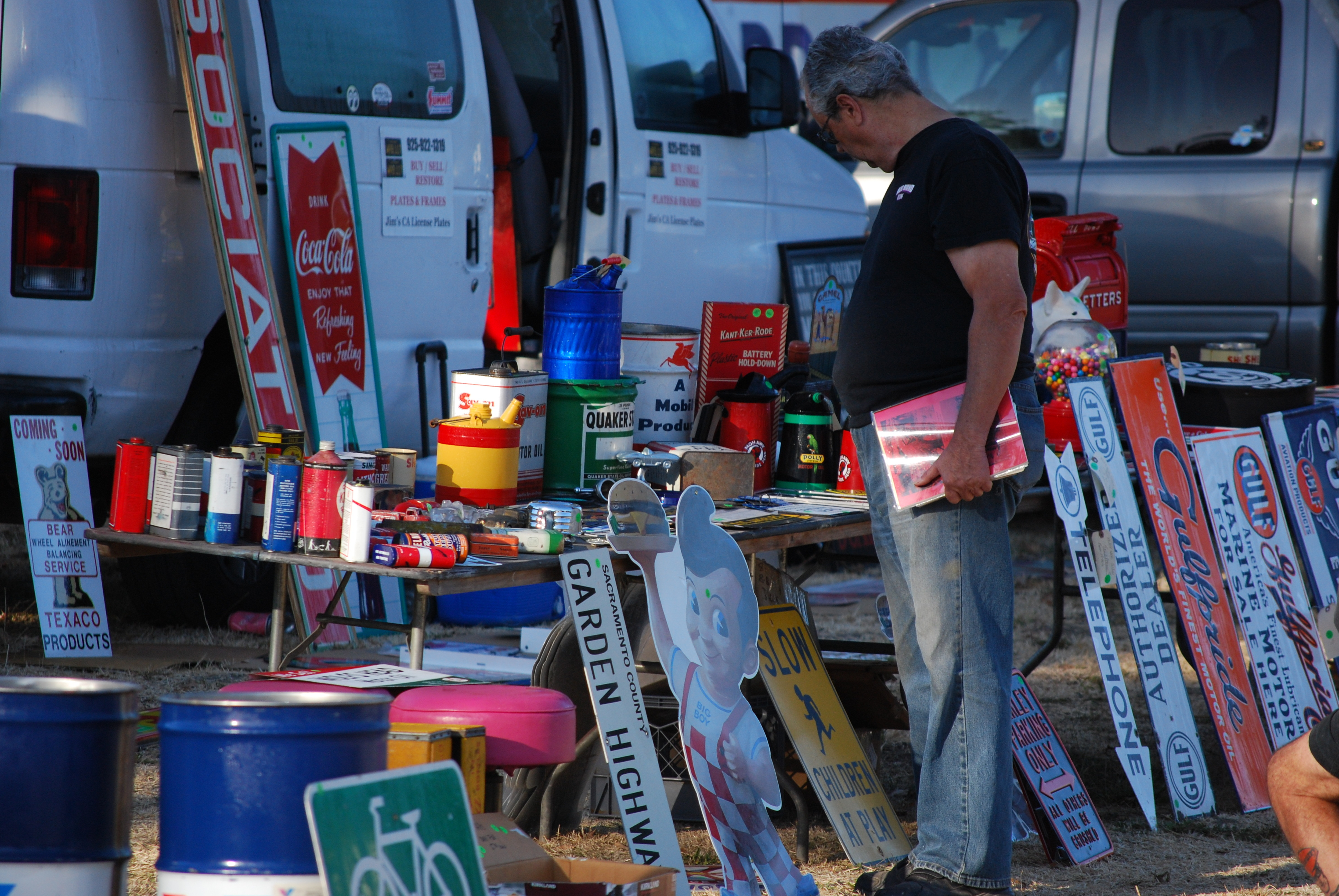 Man picking through old gas and oil bottles and gas station signage at Stoke's Ranch, the venue for the Pacific Coast Gas Bash and Swapmeet 2018